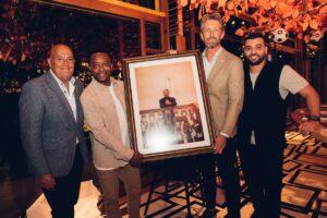 Edwin van der Sar krijgt een portret overhandigd uit handen van Soufian Asafiati en Regi Blinker
